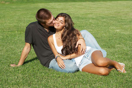 Happy young pair kissing  outdoors Фото со стока