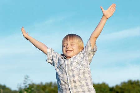pardon: Le petit gar�on aux mains tendues au ciel Banque d'images