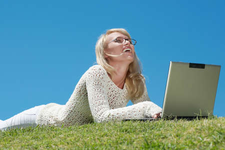 Happy young women smiling and working on a laptop outdoors Stock Photo - 5482187