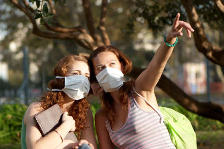 Young students in medical masks in park  photo
