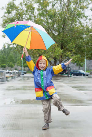 exhilaration: The boy with an umbrella standing under a rain