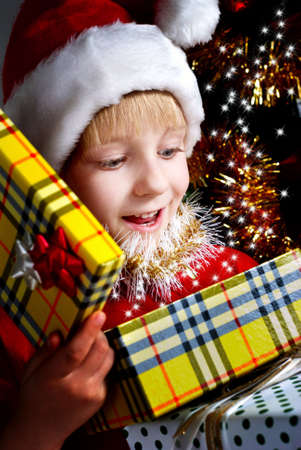 Small Santa Klaus with gifts in hands photo