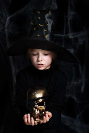 The small magician with a gold skull of dead pirate Stock Photo - 5597219