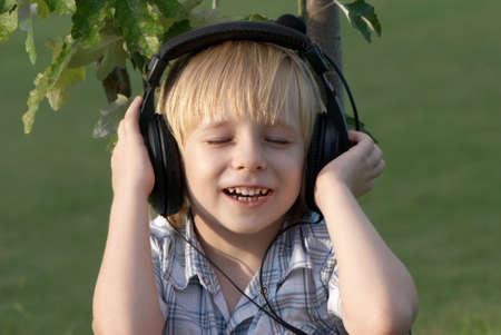 music therapy: Chico tranquilo escuchando m�sica en el parque