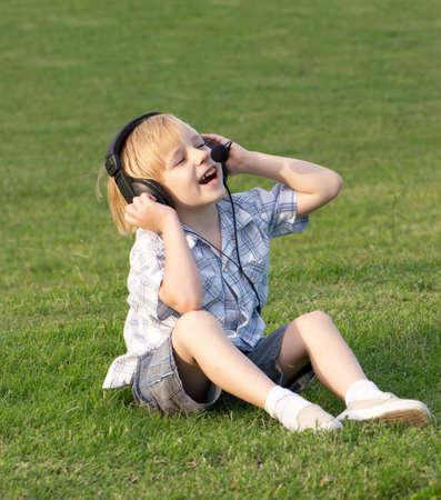 musicoterapia: Rilassante piccolo ragazzo ascolto musica nel parco  Archivio Fotografico