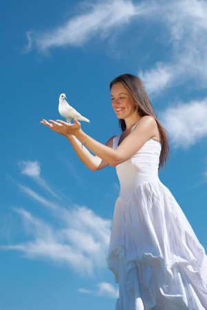 The happy woman releasing a pigeon in sky
