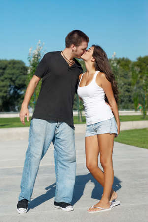 Happy young pair kissing outdoors photo