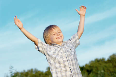 The little boy with stretched hands to sky photo