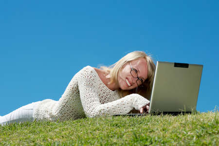 Happy young women smiling and working on a laptop outdoors Stock Photo - 5707495