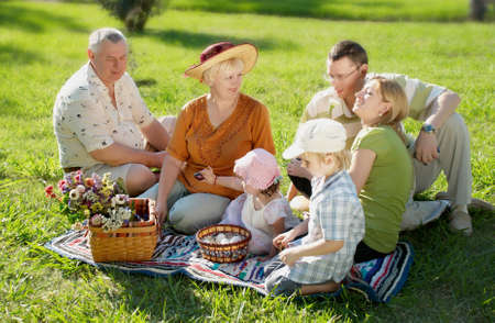 Happy family on a glade in park photo
