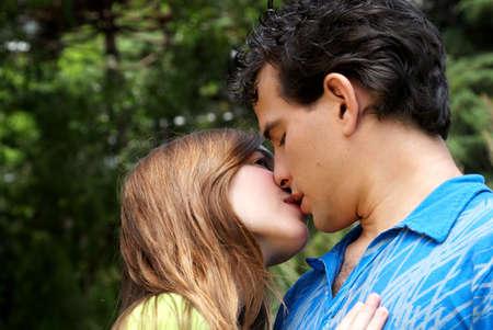 young couple kiss: Escena rom�ntica de una joven pareja contra la naturaleza
