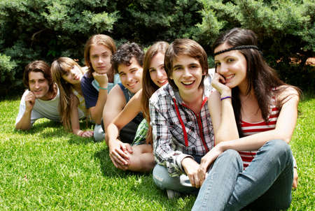 happy group of friends smiling outdoors in a park Stock Photo