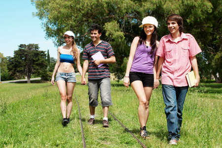 Two young couples of students going along a railroad line photo