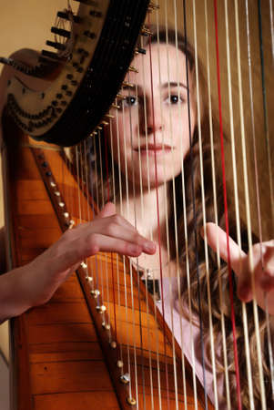 Female musician playing the harp  Stock Photo