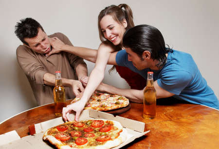 The cheerful company of youth eating a pizza photo