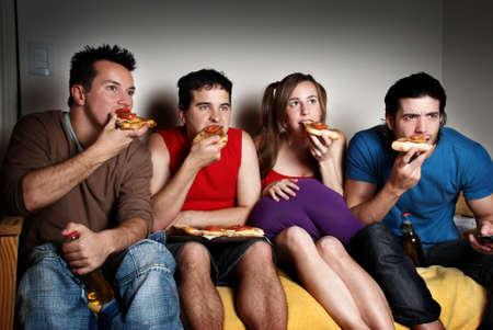 Koncentrat wentylatorów z pizza w ręce, oglądaniem telewizji