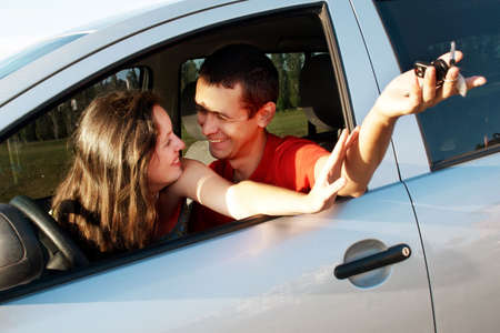 Happy young pair in just bought car photo