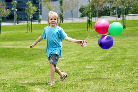 The little boy running on a grass with balloons photo