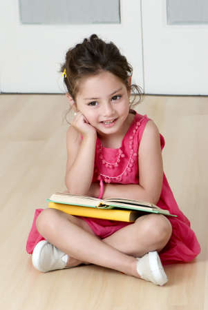 latin child: preschooler with book in kindergarten