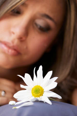 distressing: The lonely girl with a flower. Focus on a flower