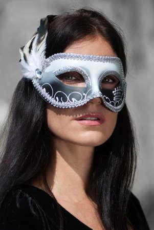 Portrait beautiful woman in black dress wearing carnival mask photo