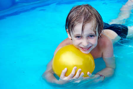 Young boy swimming in a pool photo