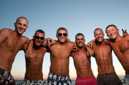 friends laughing: Joyful team of friends having fun at the beach