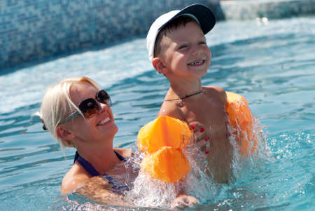 Smiling beautiful woman and little boy bathes in pool  photo
