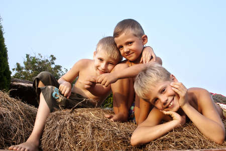 boys sitting on a hay bale on sky background  Stock Photo