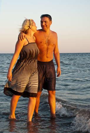Happy couple walking on the beach  photo