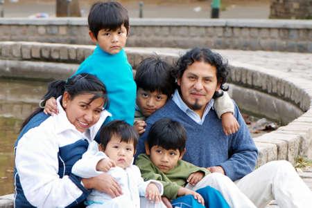 Happy Latin family sitting in the street photo