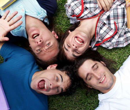 Young guys and girls lying on grass   photo