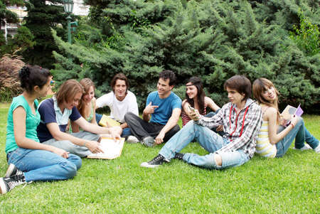 Group of students sitting in park on a grass photo