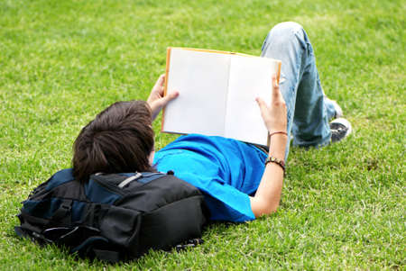 guy laying on the grass and reading a book  photo