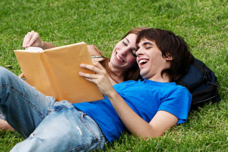 Couple students laying on the grass and reading a book photo