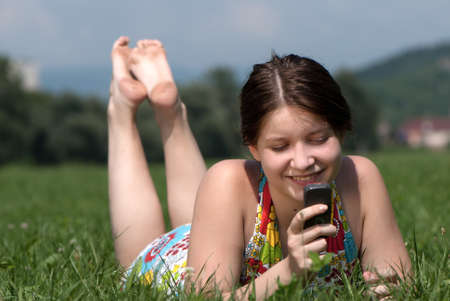 Girl speaks by mobile phone against summer green nature photo