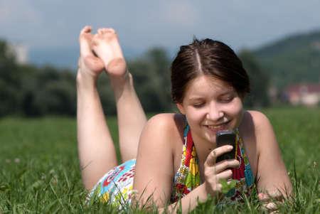 speaks: Girl speaks by mobile phone against summer green nature