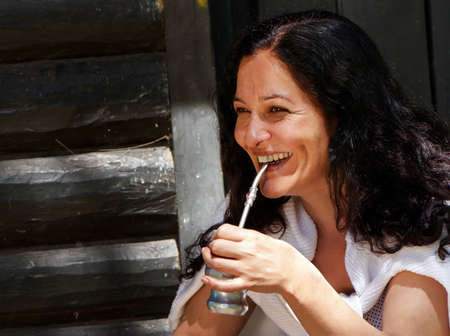 Mate: Portrait of the Latin American woman drinking a mate Stock Photo