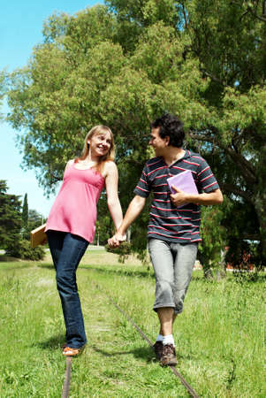 Happy young couples going along a railroad line