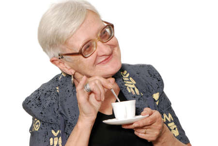 octogenarian:  Portrait of the old woman with a coffee cup on a light background   Portrait of the old woman with a coffee cup on a light background