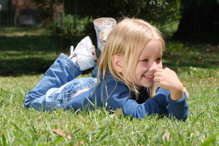 blonde little girl: The little girl laying on a grass in park  Stock Photo