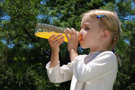 The girl drinks water from a bottle against park Stock Photo - 8789370