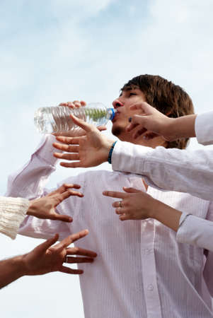 Young with bottle water against the sky and Hands reaching for water photo
