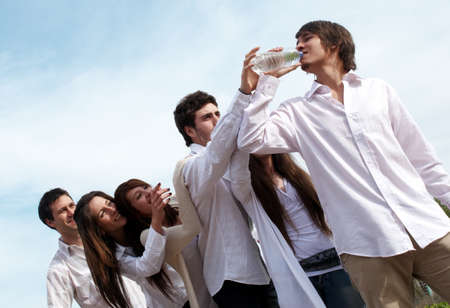 shortage: Group of young men stretching hands to a bottle with water   Stock Photo