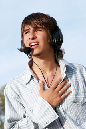 man with long hair: Singing teenage boy in headphones against the nature