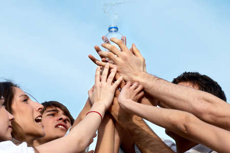 Group of young men stretching hands to a bottle with water photo