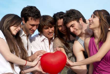 Group of young guys and girls with a sphere in the form of heart photo