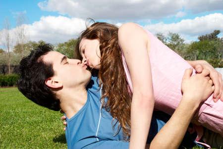besos apasionados: Feliz pareja joven bes�ndose en el parque en la hierba Foto de archivo