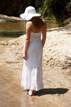 harmonous: The young girl in white going on sand Stock Photo