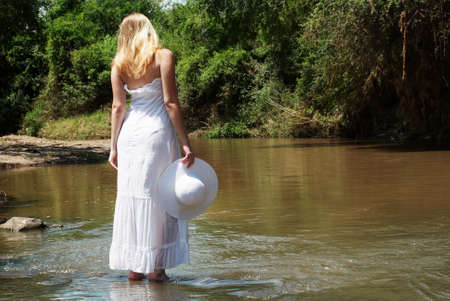 The young girl in white going on river photo